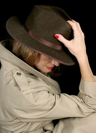 private detective: A beautiful, mysterious woman in a trenchcoat and fedora hat, turned away so her face is hidden. Stock Photo