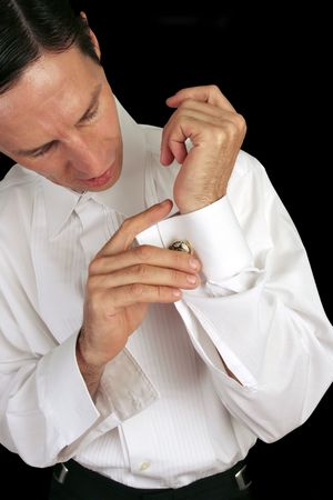 A handsome man putting on his cufflinks as he dresses in formal attire. photo