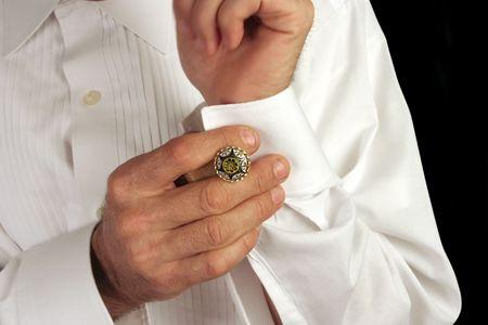 wrist cuffs: A man putting on antique cufflinks as he gets dressed in formal wear