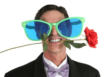 oversized: A man in a tuxedo with a rose in his mouth and oversized sunglasses
