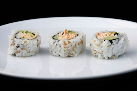 Three pieces of california roll on a white plate with black background. Stock Photo - 300729