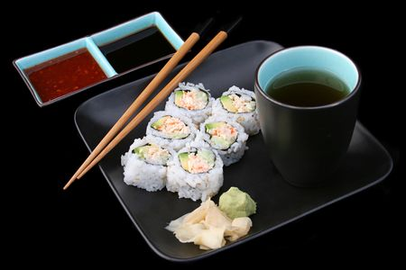 A complete sushi meal with tea on black. photo