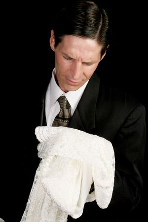 mortician: A groom left at the altar, or grieving widower, holding the empty wedding dress of his bride.