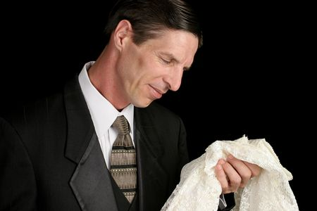 A grieving widower holding his wife's dress and smiling sadly as he remembers her.