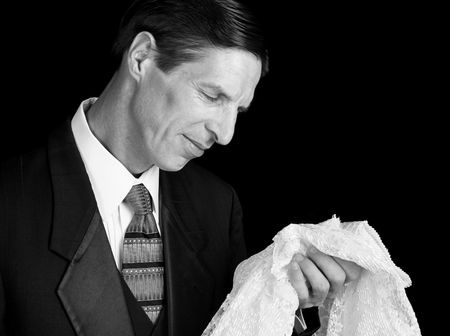 A grieving widower holding his wife's dress and smiling sadly as he remembers her. Stock fotó