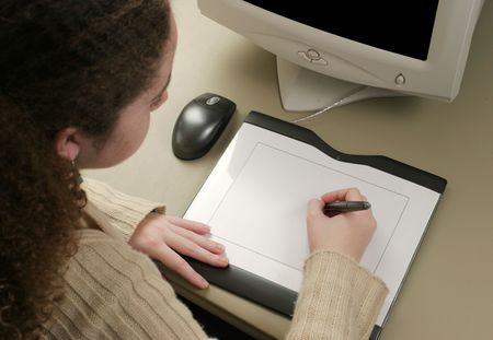 educational tools: A girl using a graphic tablet to draw on the computer. Stock Photo