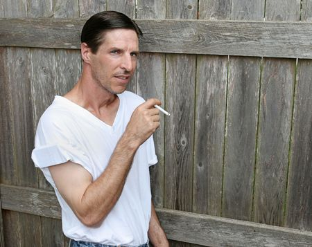 A bored looking man smoking a cigarette, leaning against a fence.  Room for text. photo