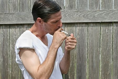 A man lighting up a cigarette. photo