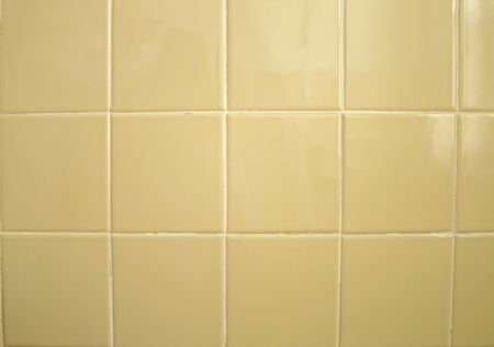 grout: A background of greenish yellow bathroom tile.  Grout needs repair. Stock Photo
