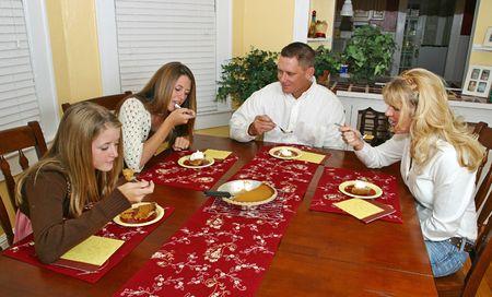 A family sitting around the dinner table enjoying pumpkin pie.