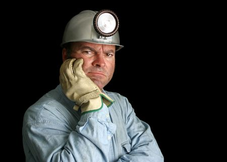 A coal miner in a dark mineshaft, looking unhappy and disgruntled. photo