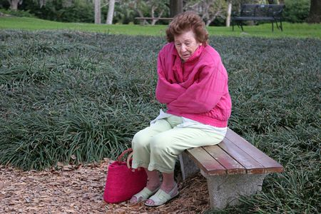 A senior woman shivering in the cold, alone on a park bench. Stock Photo