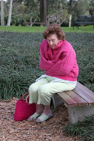 A  senior citizen shiverring in the cold on a park bench. photo