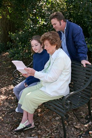 generational: A senior citizen showing a troubling letter to her son and granddaughter. Stock Photo