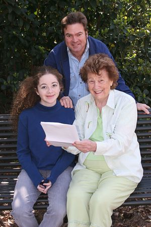 A father, daughter and grandmother reading good news together. photo
