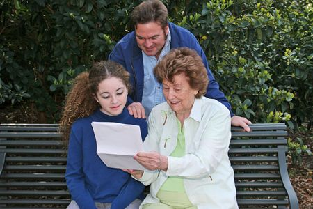 teenaged girls: A father, daughter and grandmother reading together in the park.  Horizontal orientation.