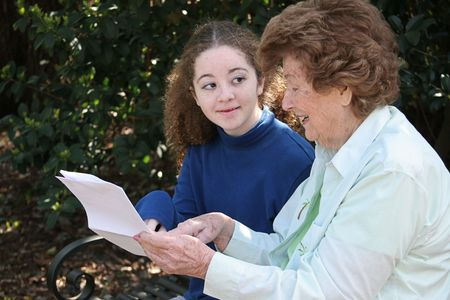 A young girl discussing homework with her grandmother. photo