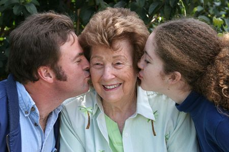A sweet grandmother receiving kisses from her family. photo