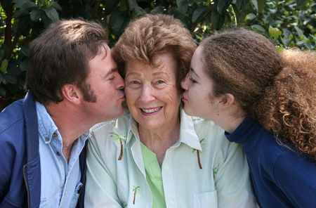 generational: A pretty grandmother receiving kisses from her family and smiling.