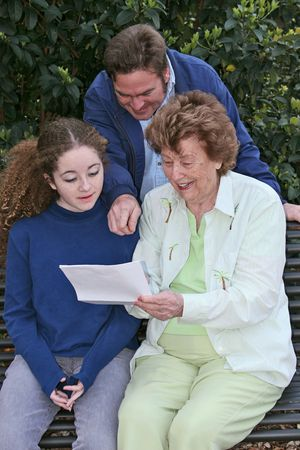 A family, father, daughter and grandmother, reading a letter containing good news. photo
