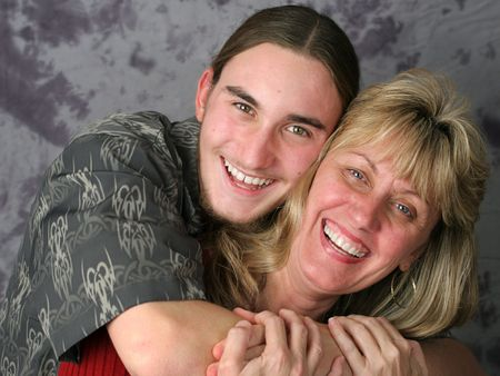 Una madre feliz y el hijo adolescente riendo y abrazando.  Foto de archivo - 327874