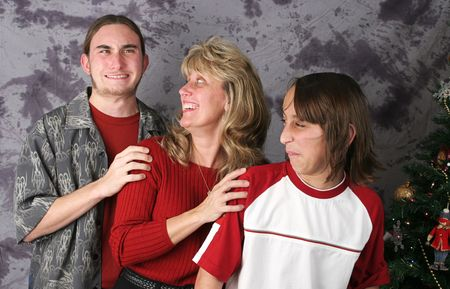 embarassment: A family posing for a Christmas portrait.  The older son has just passed gas and the mother and younger son are reacting. Stock Photo