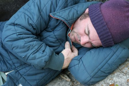 defenseless: A closeup view of a homeless man sleeping on the ground.