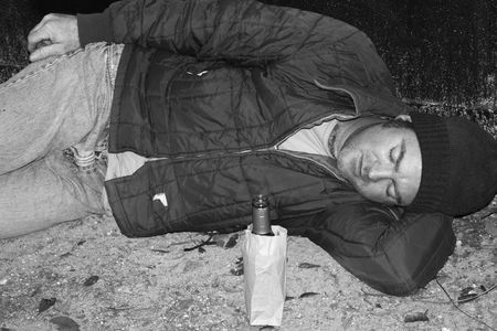 dumpster: A black and white photo of a homeless man sleeping on the ground by a dumpster.  He has a bottle of wine in a bag beside him.