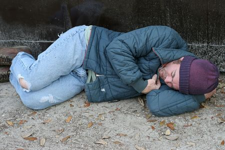 A homeless man sleeping on the ground beside a dumpster. Stockfoto