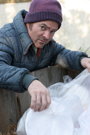 dumpster: A homeless man looking for food in a garbage dumpster.  Vertical view. Stock Photo