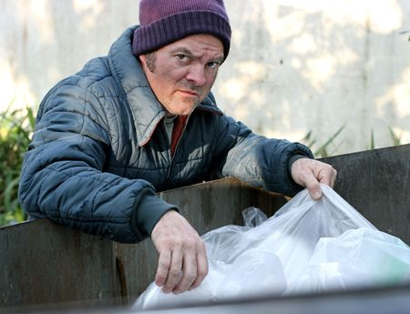 A homeless man rooting in a dumpster for food.