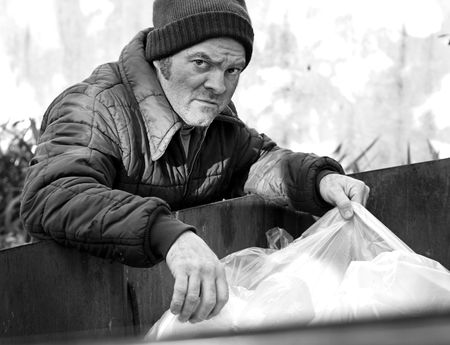 wino: A homeless man rooting in a dumpster for food. Black and White. Stock Photo