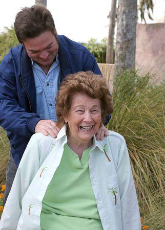 weary: A lovely senior woman enjoying a back massage in the garden.