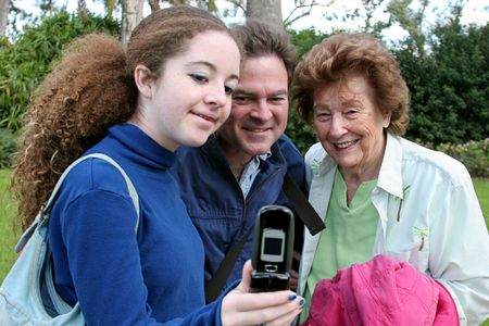 generational: A teen girl shows her new camera phone to her dad and grandma. Stock Photo