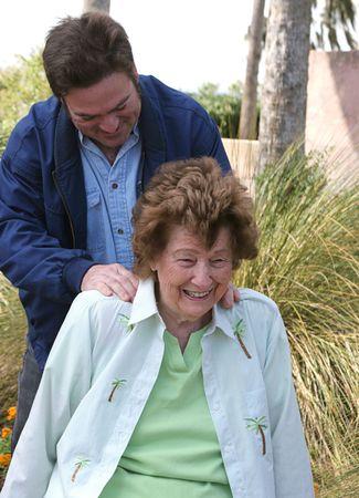 A pretty senior woman receiving a massage in the garden. photo
