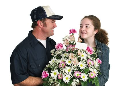 A cute teen girl receiving a bouquet of flowers from a delivery man. Isolated. photo