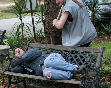 A homeless man sleeping on a park bench and a young man about to beat him with a bat. Stock Photo