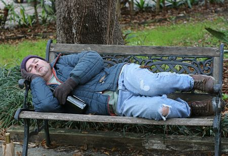 defenseless: A full view of a homeless man asleep on a park bench with his wine bottle.