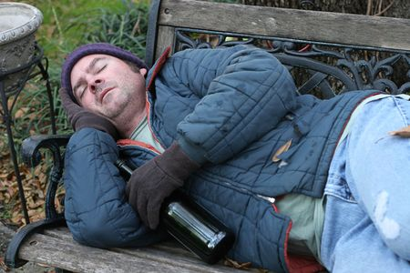 A homeless man asleep on a park bench with a bottle of wine. Stock Photo