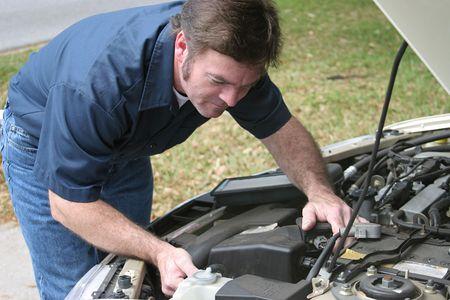An auto mechanic checking the engine of a car. Horizontal.