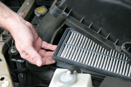 An auto mechanic removing the dirty air filter from an automobile. photo