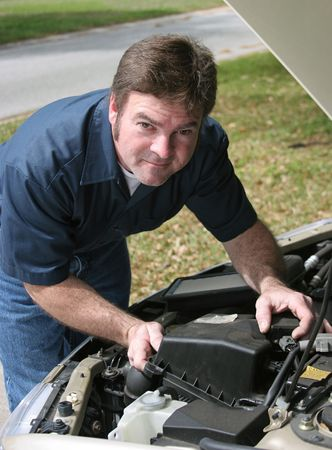 maintain: A handsome auto mechanic checking under the hood of a car.  Vertical