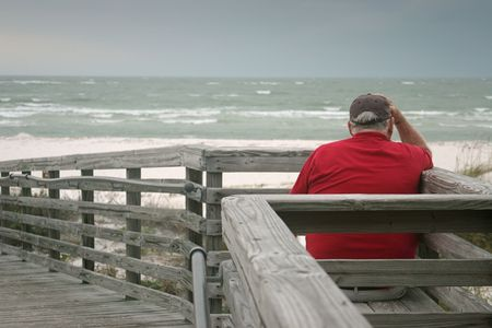 lonely man: A bored old man, watching the a storm roll in over the ocean. Stock Photo