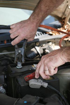 A closeup of a mechanics hands using jumper cables on a car battery. photo