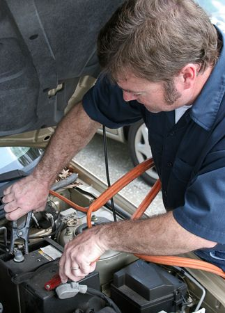 A mechanic using jumper cables to start a car battery.  Vertical. photo