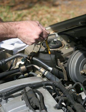 Een close-up van een monteur de hand te trekken op de oliepeilstokopening om na te gaan of een auto van de olie.