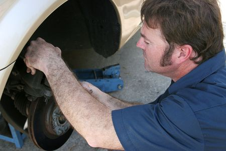 A mechanic working on a cars brakes. photo