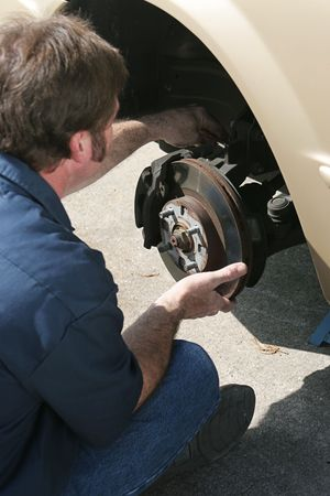A mechanic adjusting the brakes on a car.