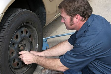 A mechanic removing lug nuts from a tire. (focus on mechanic's face & hands slightly blurred to show movement) Stock Photo - 356162