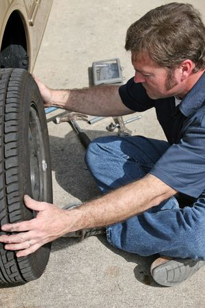 An auto mechanic removing a car tire. photo